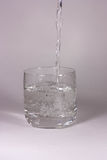 Wasser wird in ein Glas gegossen stockfotografie