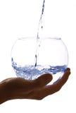 Wasser wird in ein großes Glas gegossen Stockbild