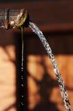 Wasserabflußrinnetülle mit fließendem Wasser Lizenzfreie Stockfotografie