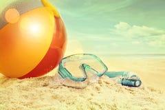 Wasserball und Schutzbrillen im Sand Stockfoto