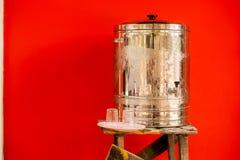 Wasserbehälter durch rote Wand Lizenzfreie Stockfotografie