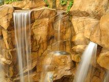 Wasserfälle an der Hintergrundeinstellung der steilen Klippe Stockfotografie