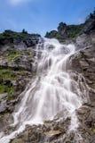 Wasserfall in den Bergen mit blauem Himmel