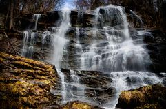 Wasserfall, der über Moos im Winter kaskadiert stockbilder
