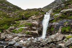 Wasserfall, der in Berge fließt Stockbild