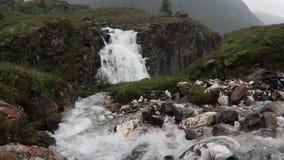Wasserfall, der in die Berge von Felsen und in grünes Gras nebelhafter Landschaft Islands fließt stock footage