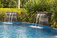 Wasserfall, der in einen blauen LagunenSwimmingpool im Hotel fällt Lizenzfreie Stockfotos