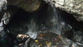 Wasserfall in der Höhle hinter Felsen im Wald stock video footage