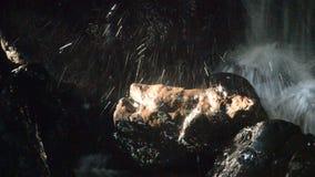 Wasserfall in der Höhle hinter Felsen im Wald stock footage