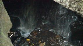 Wasserfall in der Höhle hinter Felsen im Wald stock video