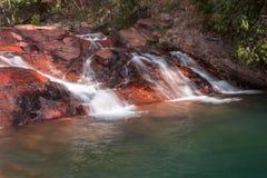 Wasserfall, der unten über Felsen fließt Stockfotos