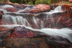 Wasserfall, der unten über Felsen fließt Stockbilder
