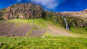 Wasserfall, der von den Bergen, Island fließt Stockbilder