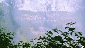 Wasserfall in der vorderen Kamera, Spritzen Ansicht der Stadt im Hügelland Kleine Häuser Sonniger Tag des Sommers stock video footage