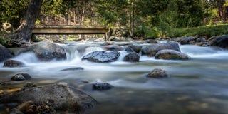 Wasserfall in einem Nebenfluss mit Bäumen und einer Brücke II lizenzfreie stockbilder