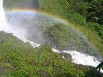 Wasserfall im äquatorialen Regenwald, mit gewölbtem Regenbogen Stockbilder