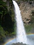 Wasserfall im äquatorialen Regenwald, mit gewölbtem Regenbogen Stockbild