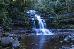 Wasserfall im Regenwald, der hinunter Felsengesicht fließt Lizenzfreie Stockfotos