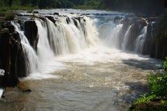 Wasserfall in Laos mit rotem Wasser Stockfotos