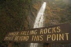 Wasserfall mit fallendem Felsenzeichen lizenzfreie stockfotos
