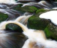 Wasserfall mit Felsen und Schnee im Wald Stockfotografie