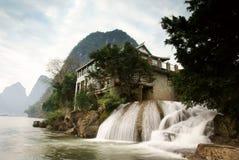 Wasserfall mit Haus Stockbilder