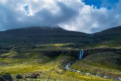 Wasserfall in Ost-Fjordsm unter einem bewölkten Himmel lizenzfreie stockbilder