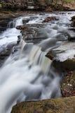 Wasserfall tief im Wald während des Winters Stockfotos