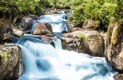 Wasserfall und blauer Strom im Wald Stockbilder