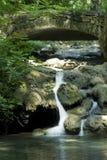 Wasserfall und Brücke Stockfotografie