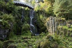 Wasserfall und Brücke im Park des Schlosses Wilhelmshoehe, Kassel, Deutschland lizenzfreie stockfotografie