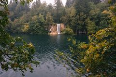 Wasserfall und ein See mit einem Stein in den Plitvice Seen national Lizenzfreie Stockbilder