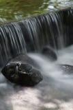 Wasserfall und Felsen Stockbild