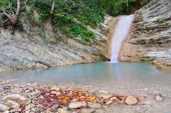 Wasserfall und gefallener Herbstlaub Lizenzfreie Stockbilder