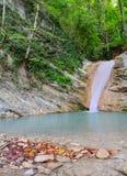 Wasserfall und gefallener Herbstlaub Lizenzfreie Stockfotos