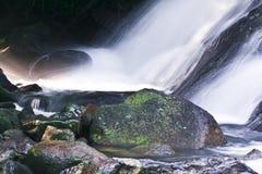Wasserfall und großer Felsen Stockbild