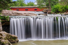 Wasserfall und rote überdachte Brücke Stockfotografie