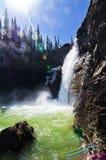 Wasserfall und Sonnenschein stockbild