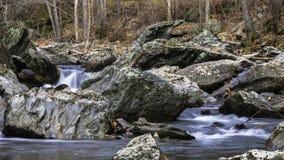 Wasserfall unter den Felsen Stockfotos