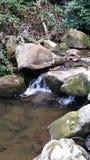 Wasserfall unter den Felsen versteckt stockbild