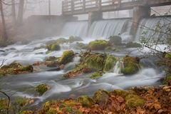 Wasserfall unter einer Brücke auf einem nebeligen Fallmorgen. Lizenzfreies Stockbild