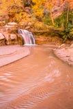 Wasserfall zum flachen Fluss unter goldenen Pappelbäumen Stockfotografie