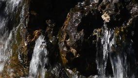 Wasserfallstrom des langsamen Wassers über felsigen Steinen stock video