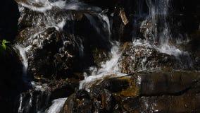 Wasserfallstrom des schnellen Wassers über felsigen Steinen stock footage