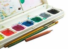 Wasserfarbkasten, -bürsten und -bleistift auf weißem Hintergrund Lizenzfreie Stockfotografie