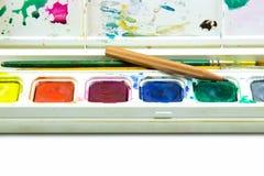 Wasserfarbkasten, -bürsten und -bleistift auf weißem Hintergrund Stockbild