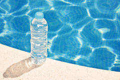 Wasserflasche durch Swimmingpool Stockfotografie