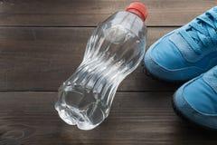 Wasserflasche und Paare Turnschuhe Stockbild