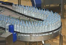 Wasserflaschen auf Flaschenabfüllmaschine ind des Förderers und des Wassers Lizenzfreie Stockfotografie