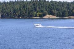 Wasserflugzeug, das in einer Ozean-Bucht startet Lizenzfreie Stockfotografie